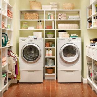 Bild på en mellanstor vintage u-formad tvättstuga enbart för tvätt, med vita skåp, beige väggar, mellanmörkt trägolv, en tvättmaskin och torktumlare bredvid varandra, brunt golv och öppna hyllor