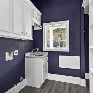 Inspiration för stora klassiska parallella grått tvättstugor enbart för tvätt, med en undermonterad diskho, släta luckor, vita skåp, marmorbänkskiva, grått stänkskydd, stänkskydd i marmor, lila väggar, klinkergolv i keramik, en tvättmaskin och torktumlare bredvid varandra och grått golv