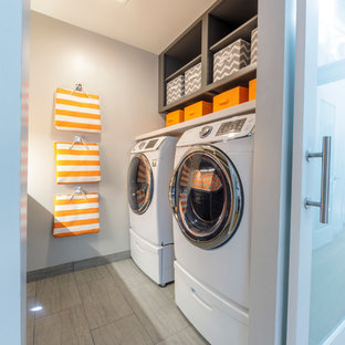 Small midcentury galley laundry room in San Francisco with an undermount sink, flat-panel cabinets, grey cabinets, quartz benchtops, grey walls, porcelain floors, a side-by-side washer and dryer, grey floor and white benchtop.
