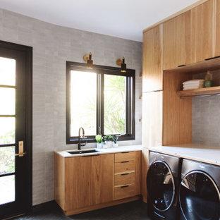 Idéer för stora funkis u-formade vitt grovkök, med en undermonterad diskho, släta luckor, skåp i ljust trä, marmorbänkskiva, grå väggar, skiffergolv, en tvättmaskin och torktumlare bredvid varandra och grått golv