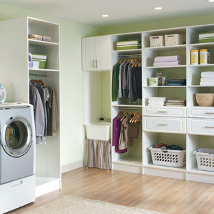 Example of a mid-sized classic l-shaped dark wood floor laundry room design in Boston with open cabinets, white cabinets, solid surface countertops, green walls and a side-by-side washer/dryer