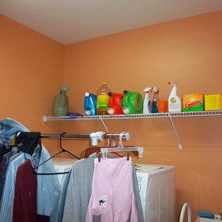 Idéer för en mellanstor modern linjär tvättstuga enbart för tvätt, med en allbänk, orange väggar och en tvättmaskin och torktumlare bredvid varandra