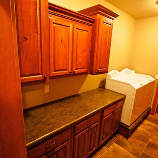 Inspiration for a mid-sized dedicated laundry room remodel in Other with raised-panel cabinets, dark wood cabinets, laminate countertops and a side-by-side washer/dryer