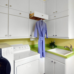 Photo of a mid-sized contemporary l-shaped dedicated laundry room in Miami with a drop-in sink, raised-panel cabinets, white cabinets, porcelain floors, a side-by-side washer and dryer, brown floor and yellow walls.