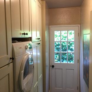 Foto di una piccola lavanderia multiuso country con ante in stile shaker, ante bianche, pareti beige, pavimento in linoleum, lavatrice e asciugatrice a colonna e pavimento beige