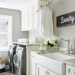 Large elegant single-wall ceramic floor and multicolored floor dedicated laundry room photo in Minneapolis with a farmhouse sink, recessed-panel cabinets, white cabinets, granite countertops, gray walls, a side-by-side washer/dryer and multicolored countertops
