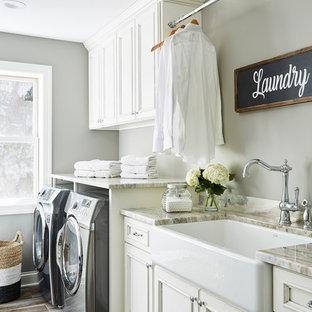 Foto på en stor vintage flerfärgade linjär tvättstuga enbart för tvätt, med en rustik diskho, luckor med infälld panel, vita skåp, granitbänkskiva, grå väggar, klinkergolv i keramik, en tvättmaskin och torktumlare bredvid varandra och flerfärgat golv