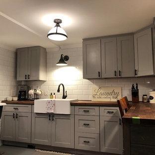 Esempio di una lavanderia multiuso moderna di medie dimensioni con lavello stile country, ante in stile shaker, ante grigie, top in legno, pareti grigie, pavimento in cemento, lavatrice e asciugatrice affiancate, pavimento grigio e top marrone