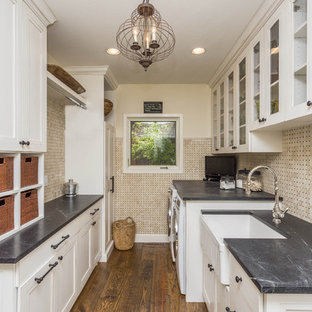 Large country galley utility room in Phoenix with a farmhouse sink, recessed-panel cabinets, white cabinets, soapstone benchtops, beige walls, medium hardwood floors, a side-by-side washer and dryer, brown floor and grey benchtop.