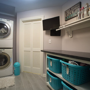Inspiration for a mid-sized traditional galley dedicated laundry room in Indianapolis with open cabinets, solid surface benchtops, purple walls, vinyl floors, a stacked washer and dryer and grey floor.