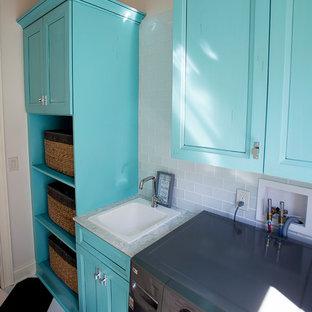 Exotisk inredning av en mellanstor parallell tvättstuga enbart för tvätt, med en nedsänkt diskho, släta luckor, blå skåp, bänkskiva i kvarts, vita väggar, vinylgolv, en tvättmaskin och torktumlare bredvid varandra och svart golv