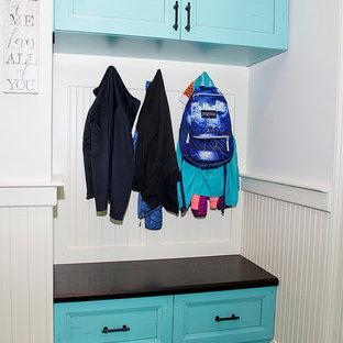 Immagine di una sala lavanderia tropicale di medie dimensioni con lavello da incasso, ante lisce, ante blu, top in quarzo composito, pareti bianche, pavimento in vinile, lavatrice e asciugatrice affiancate e pavimento nero
