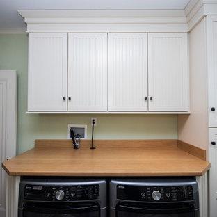 Immagine di una lavanderia multiuso tradizionale di medie dimensioni con ante a filo, ante bianche, top in laminato, pareti verdi, pavimento in vinile, lavatrice e asciugatrice affiancate e pavimento marrone