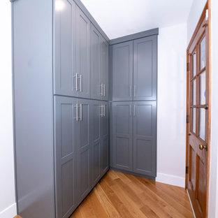 Bild på en mellanstor vintage gula u-formad gult tvättstuga enbart för tvätt, med en enkel diskho, släta luckor, grå skåp, marmorbänkskiva, vitt stänkskydd, stänkskydd i marmor, vita väggar, ljust trägolv, en tvättmaskin och torktumlare bredvid varandra och brunt golv
