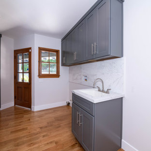 Foto på en mellanstor vintage gula u-formad tvättstuga enbart för tvätt, med en enkel diskho, släta luckor, grå skåp, marmorbänkskiva, vitt stänkskydd, stänkskydd i marmor, vita väggar, ljust trägolv, en tvättmaskin och torktumlare bredvid varandra och brunt golv