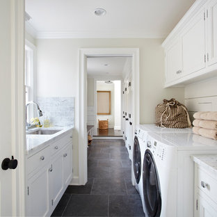 Example of a classic slate floor and black floor laundry room design in New York with white cabinets and white countertops