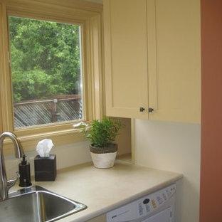 Klassisk inredning av en liten linjär tvättstuga enbart för tvätt, med en nedsänkt diskho, skåp i shakerstil, beige skåp, laminatbänkskiva, beige väggar, korkgolv och en tvättmaskin och torktumlare bredvid varandra