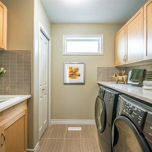 Foto di una lavanderia multiuso classica con lavello da incasso, ante in stile shaker, ante in legno chiaro, lavatrice e asciugatrice affiancate, pavimento marrone e pareti beige