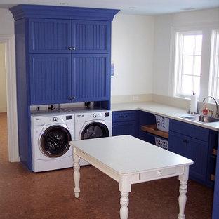 Bild på en stor lantlig tvättstuga enbart för tvätt, med skåp i shakerstil, blå skåp, vita väggar, korkgolv och en tvättmaskin och torktumlare bredvid varandra