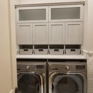 Modern inredning av ett litet grå l-format grått grovkök, med en undermonterad diskho, skåp i shakerstil, turkosa skåp, granitbänkskiva, grå väggar, marmorgolv, en tvättmaskin och torktumlare bredvid varandra och vitt golv