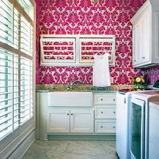 Immagine di una lavanderia multiuso tradizionale di medie dimensioni con lavello stile country, ante con riquadro incassato, ante bianche, top in granito, pareti rosa e lavatrice e asciugatrice affiancate
