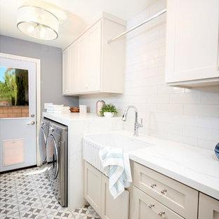 Maritim inredning av ett litet vit linjärt vitt grovkök, med en rustik diskho, luckor med infälld panel, grå skåp, bänkskiva i kvarts, vita väggar, klinkergolv i keramik, en tvättmaskin och torktumlare bredvid varandra och grått golv