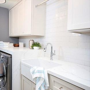 Inspiration för ett litet maritimt vit linjärt vitt grovkök, med en rustik diskho, luckor med infälld panel, grå skåp, bänkskiva i kvarts, vita väggar, klinkergolv i keramik, en tvättmaskin och torktumlare bredvid varandra och grått golv