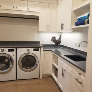 マイアミの広いトランジショナルスタイルのおしゃれな家事室 (L型、アンダーカウンターシンク、落し込みパネル扉のキャビネット、白いキャビネット、クオーツストーンカウンター、ベージュの壁、無垢フローリング、洗濯乾燥機、ベージュの床、青いキッチンカウンター) の写真