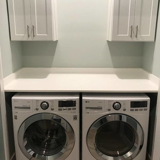 Photo of a mid-sized traditional single-wall dedicated laundry room in Jacksonville with shaker cabinets, white cabinets, beige walls, porcelain floors, a side-by-side washer and dryer, black floor and white benchtop.