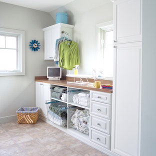 Inspiration for a mid-sized contemporary single-wall ceramic tile utility room remodel in New York with raised-panel cabinets, white cabinets, wood countertops and white walls