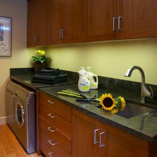 Immagine di una lavanderia chic con lavello a vasca singola, ante in legno scuro, top in granito, pareti gialle, pavimento in bambù e lavatrice e asciugatrice affiancate
