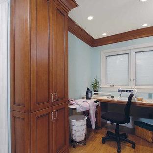 Immagine di una lavanderia classica con ante in legno scuro, top in laminato, pareti blu, pavimento in bambù e lavatrice e asciugatrice nascoste