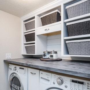 Idéer för ett litet lantligt grå linjärt grovkök, med öppna hyllor, vita skåp, träbänkskiva, vita väggar, klinkergolv i porslin, en tvättmaskin och torktumlare bredvid varandra och beiget golv