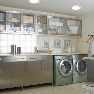 Immagine di una lavanderia multiuso classica di medie dimensioni con ante di vetro, ante in acciaio inossidabile, top in granito, pareti beige, pavimento con piastrelle in ceramica e lavatrice e asciugatrice affiancate