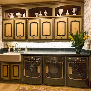 Immagine di una grande sala lavanderia vittoriana con lavello stile country, ante con bugna sagomata, ante in legno chiaro, top in saponaria, pavimento in pietra calcarea e lavatrice e asciugatrice affiancate