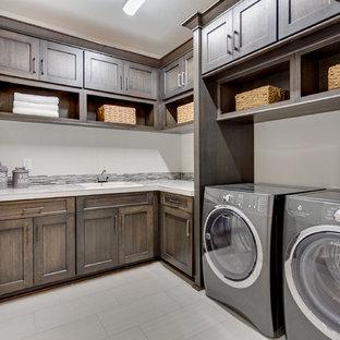 Exempel på ett mellanstort klassiskt l-format grovkök, med en nedsänkt diskho, luckor med infälld panel, skåp i mörkt trä, kaklad bänkskiva, grå väggar, klinkergolv i porslin och en tvättmaskin och torktumlare bredvid varandra