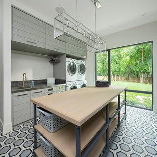 Inspiration for a large modern single-wall utility room in Salt Lake City with a submerged sink, flat-panel cabinets, grey cabinets, engineered stone countertops, white walls and a stacked washer and dryer.