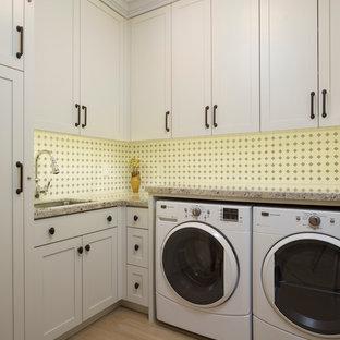 Foto di una grande sala lavanderia stile americano con lavello sottopiano, ante con riquadro incassato, ante bianche, top in granito e lavatrice e asciugatrice affiancate