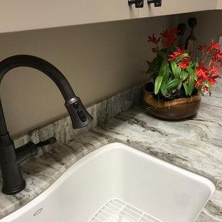 Foto di una sala lavanderia tropicale di medie dimensioni con lavello sottopiano, ante con riquadro incassato, ante grigie, top in granito, pareti grigie, pavimento con piastrelle in ceramica, lavatrice e asciugatrice affiancate, pavimento beige e top grigio