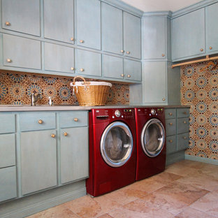 Photo of a large mediterranean l-shaped separated utility room in Dallas with flat-panel cabinets, blue cabinets, a side by side washer and dryer, pink floors, limestone flooring and multi-coloured walls.