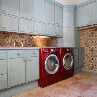 Пример оригинального дизайна: большая отдельная, угловая прачечная в средиземноморском стиле с плоскими фасадами, синими фасадами, со стиральной и сушильной машиной рядом, розовым полом, полом из известняка и разноцветными стенами