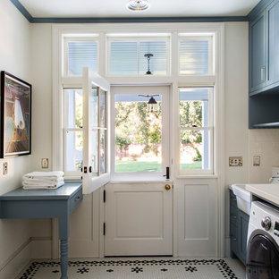 Exemple d'une grand buanderie linéaire chic avec un évier de ferme, un placard à porte shaker, des portes de placard bleues, un mur blanc, des machines côte à côte, un plan de travail en quartz, un sol en carrelage de céramique, un sol multicolore et un plan de travail blanc.