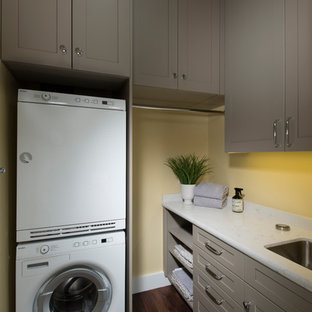 Foto på en liten amerikansk l-formad tvättstuga enbart för tvätt, med en undermonterad diskho, luckor med infälld panel, grå skåp, bänkskiva i kvarts, gula väggar, vinylgolv, en tvättpelare och brunt golv
