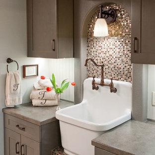 Cette image montre une petit buanderie parallèle craftsman multi-usage avec un évier de ferme, un placard à porte shaker, des portes de placard grises, un mur gris, un sol en vinyl et des machines superposées.