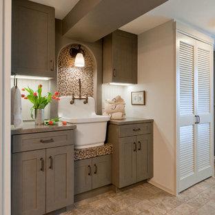 Réalisation d'une petite buanderie parallèle craftsman multi-usage avec un évier de ferme, un placard à porte shaker, des portes de placard grises, un mur gris, un sol en vinyl et des machines superposées.