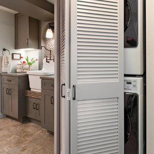 Small arts and crafts galley vinyl floor utility room photo in Seattle with a farmhouse sink, shaker cabinets, gray cabinets, laminate countertops, gray walls and a stacked washer/dryer