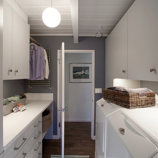 This is an example of a small contemporary galley separated utility room in San Francisco with flat-panel cabinets, marble worktops, grey walls, a side by side washer and dryer and white cabinets.