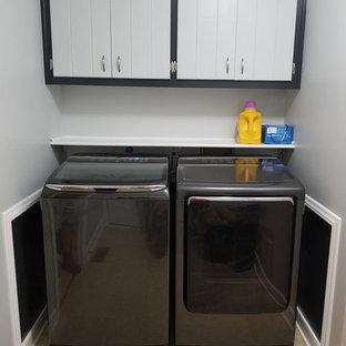 Immagine di una lavanderia minimalista con pareti grigie, pavimento in laminato, lavatrice e asciugatrice affiancate e pavimento beige