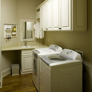 Mid-sized elegant l-shaped medium tone wood floor and brown floor dedicated laundry room photo in Philadelphia with a drop-in sink, raised-panel cabinets, white cabinets, beige walls, a side-by-side washer/dryer, quartz countertops and beige countertops