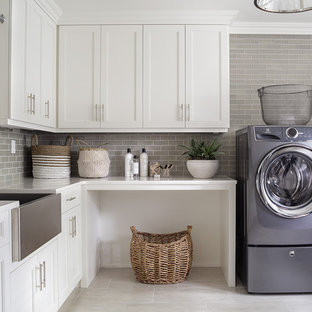 Example of a large classic u-shaped ceramic tile and gray floor dedicated laundry room design in New York with an utility sink, shaker cabinets, white cabinets, quartz countertops, gray walls, a side-by-side washer/dryer and white countertops